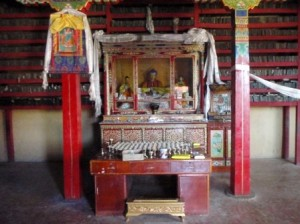 An altar in the Narthang Monastery; the library of scripture printing tablets in the background.