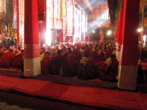 The sunlight streams through the butter-candle smoke and incense onto the chanting monks.